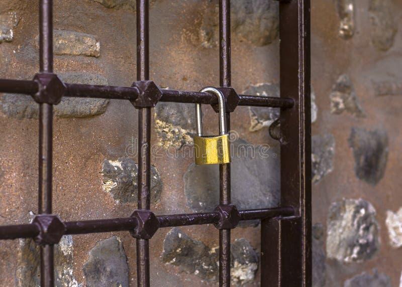 Vorhängeschloß auf dem Gitter Antiker Metallgrill, auf dem ein goldenes Schloss gegen eine Steinwand wiegt lizenzfreies stockfoto