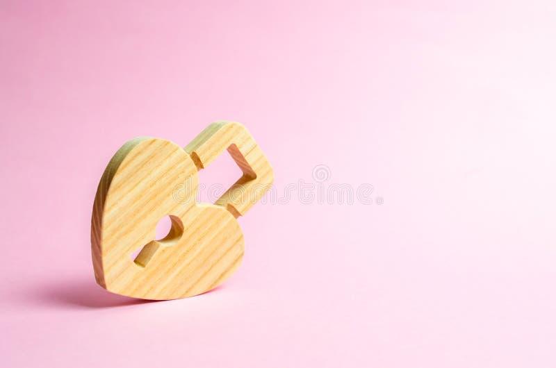 Vorhängeschloß in Form eines Herzens auf einem rosa Hintergrund Das Geheimnis von Verhältnissen und von Aufnahmenregeln Starkes L stockfotos