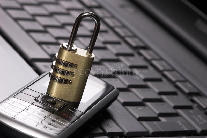 Vorhängeschloßanzeigen-Handy auf Laptop lizenzfreie stockfotos