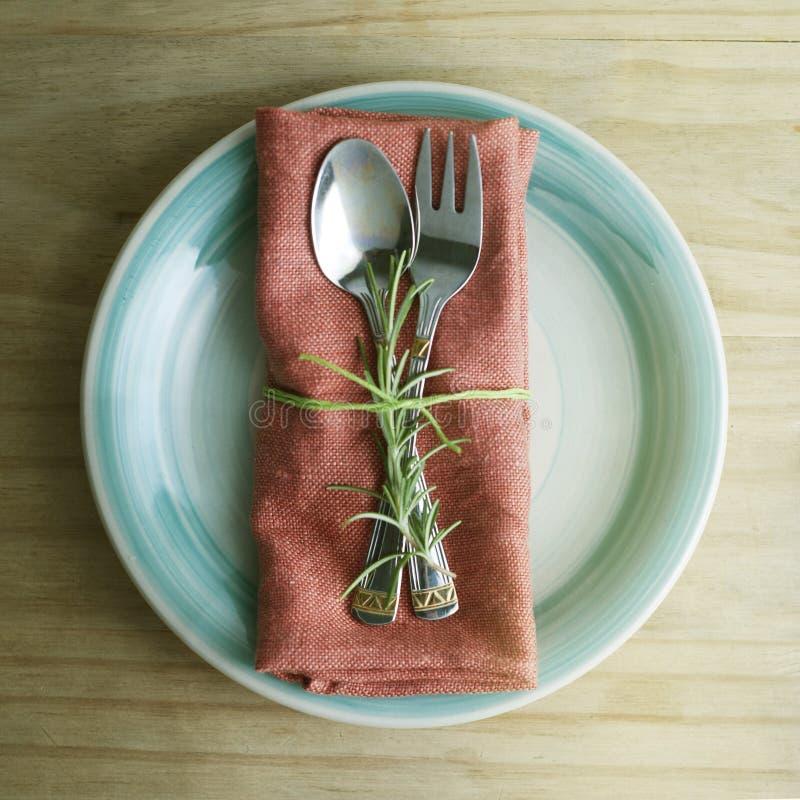 Vork en lepel op ronde plaat met servet, met een takje van rozemarijn Rustieke houten achtergrond Voedselonderwijs Gezond voedsel royalty-vrije stock afbeeldingen