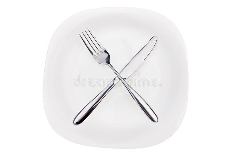 Vork en mes op een schotel royalty-vrije stock foto