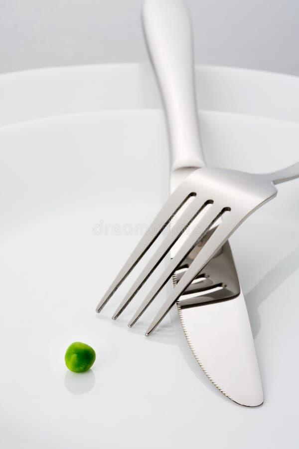 Vork, mes en één enkele groene erwt op een plaat royalty-vrije stock foto