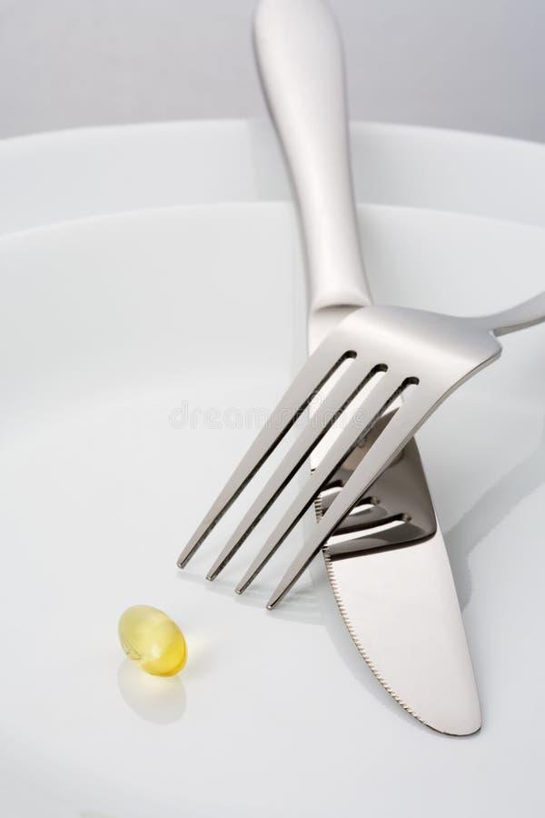 Vork, mes en één enkele vistraan capsulel op een plaat royalty-vrije stock afbeeldingen