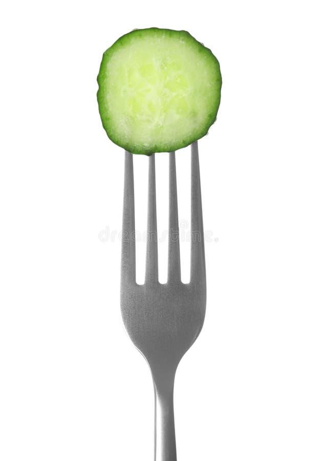 Vork met komkommerplak op wit stock foto's