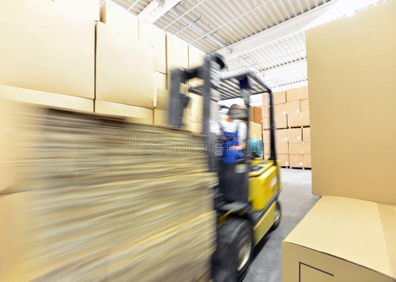 Vorkheftruckbestuurder in een pakhuis voor industriële goederen stock foto's