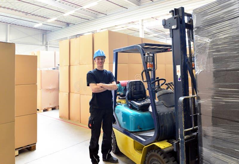 Vorkheftruckbestuurder in een pakhuis voor industriële goederen royalty-vrije stock afbeeldingen