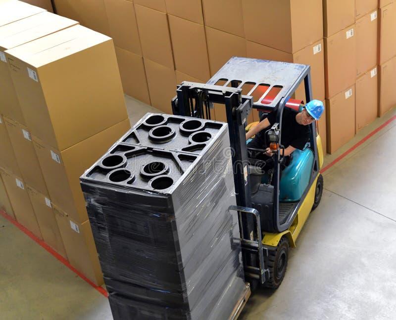 Vorkheftruckbestuurder in een pakhuis voor industriële goederen royalty-vrije stock fotografie