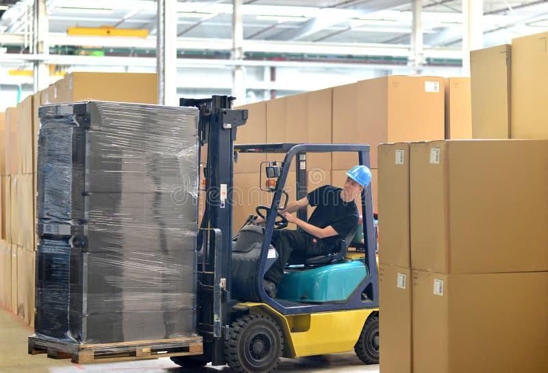 Vorkheftruckbestuurder in een pakhuis voor industriële goederen stock fotografie