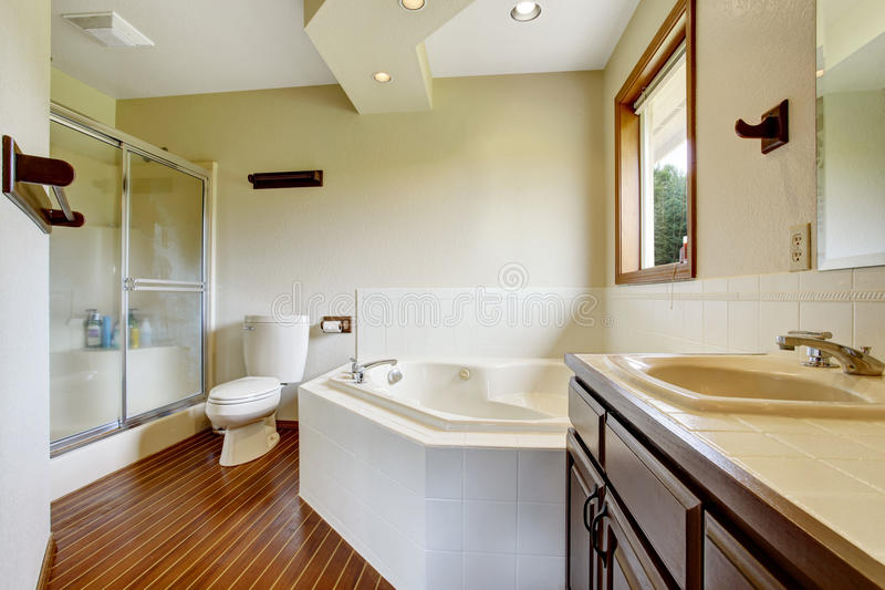 Vorlagenbadezimmerinnenraum mit Glasdusche, Massivholzboden und weiße Badewanne mit Fliese trimmen stockbilder