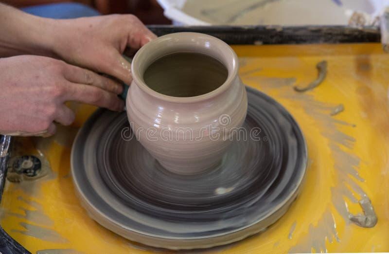 Vorlagenklasse auf der Herstellung eines keramischen Topfes mit einer T?pferscheibe Die Tonwaren drehen sich um seine Achse stockfoto