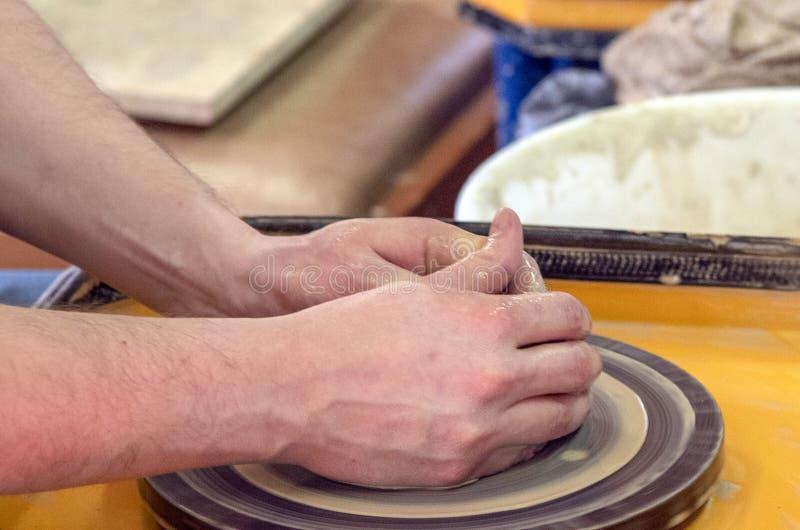 Vorlagenklasse auf der Herstellung eines keramischen Topfes mit einer T?pferscheibe Die Tonwaren drehen sich um seine Achse stockfotos