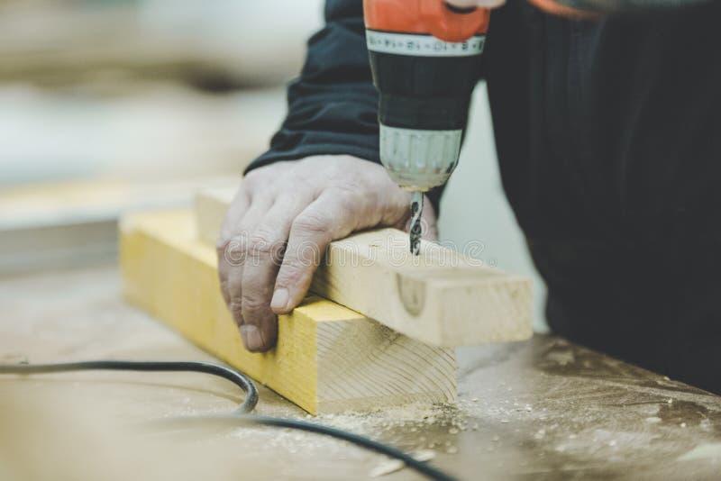 Vorlagentischler, der an Holzarbeit unter Verwendung der Elektrowerkzeuge arbeitet stockbild