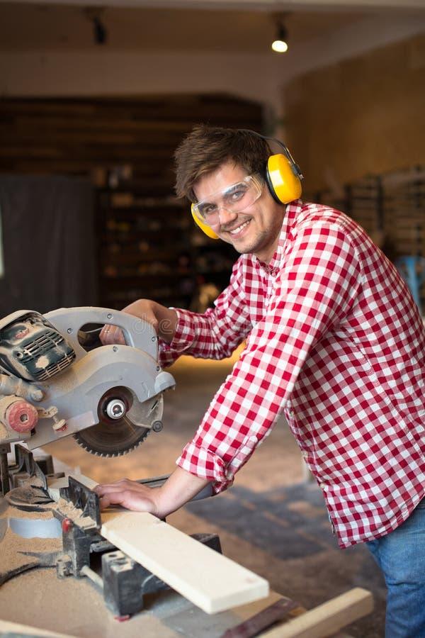 Vorlagentischler mit Kopfhörern und Gläsern sägt Brett circula lizenzfreie stockfotos