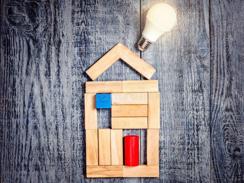 Vorm van huis boven boom op donkere houten achtergrond en LEIDENE bol Imitatie van het verwarmen van koper of boiler en aircondit royalty-vrije stock afbeelding