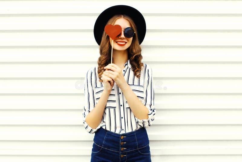 Vormde de portret gelukkige glimlachende jonge vrouw die haar oog met rood hart verbergt lolly in zwarte ronde hoed, wit gestreep stock afbeeldingen