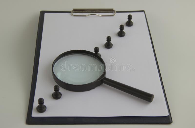 Vormen en een vergrootglas het personeel u van het conceptenbeheer en rekrutering stock afbeelding