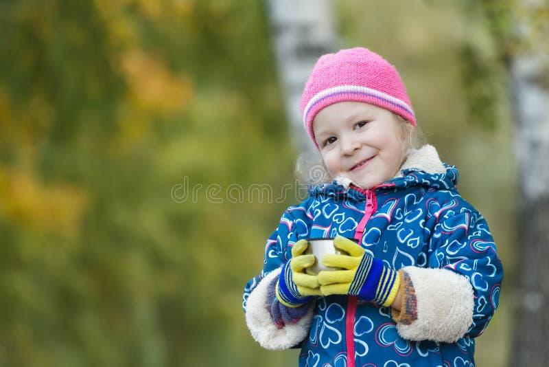 Vormen het dalings openluchthoofd en het schoudersportret van het staalthermosfles van de meisjeholding in handen tot een kom stock foto