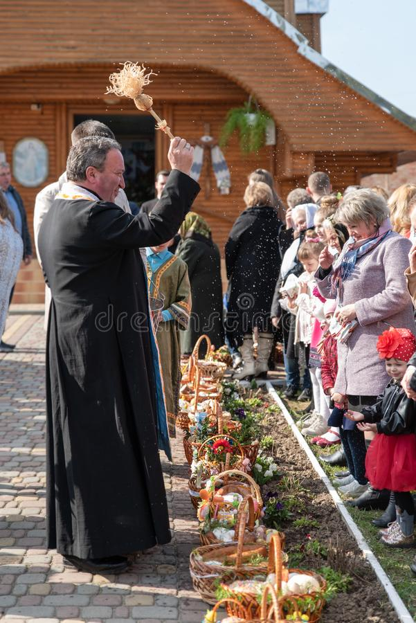 Voroblevychi village, Drohobych district, Western Ukraine - April 07, 2018: Priest consecrates Easter baskets. With food. Christians near the temple. Traditions royalty free stock images