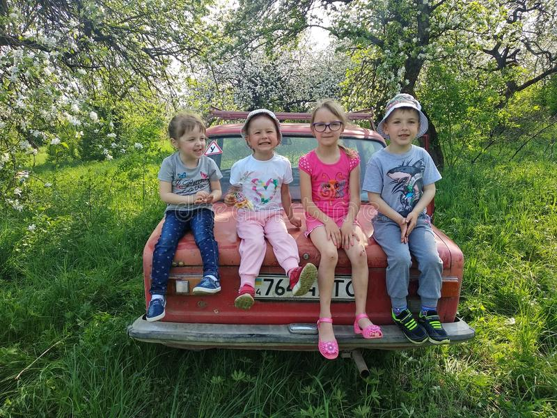 Voroblevychi village, Drohobych, Ukraine - May 29, 2018: Children fun on trunk of old car in the garden, springtime royalty free stock images