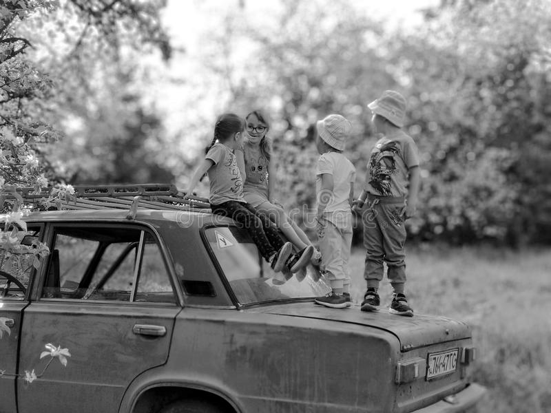 Voroblevychi village, Drohobych, Ukraine - May 29, 2018: Children fun on trunk of old car, the natural environment stock image