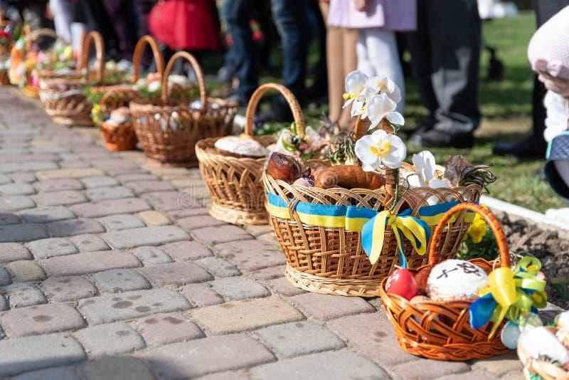 Voroblevychi wioska, Drohobych okręg Ukraina, Kwiecień, - 07, 2018: Wielkanocni kosze z karmowym pobliskim kościół zdjęcia stock