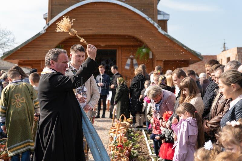 Voroblevychidorp, Drohobych-district, de Oekraïne - April 07, 2018: De priester zegent Pasen-manden met voedsel stock fotografie