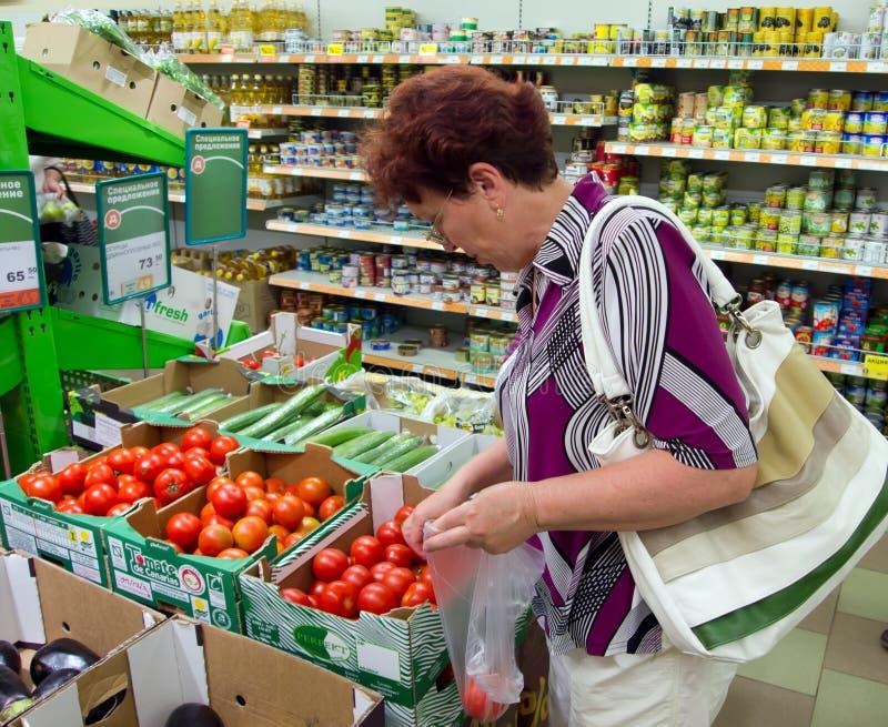 Voronež, Russia - 20 giugno 2013, la donna matura sceglie il pomodoro in supermercato fotografia stock libera da diritti