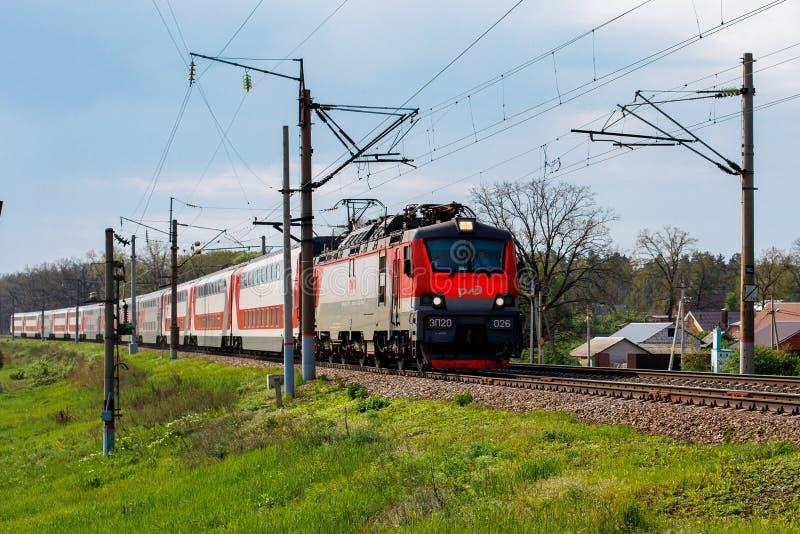 Voronež, Russia: 14 maggio 2019 Una locomotiva elettrica tira un treno passeggeri sero-rosso Nella priorità alta, erba verde, in immagini stock libere da diritti