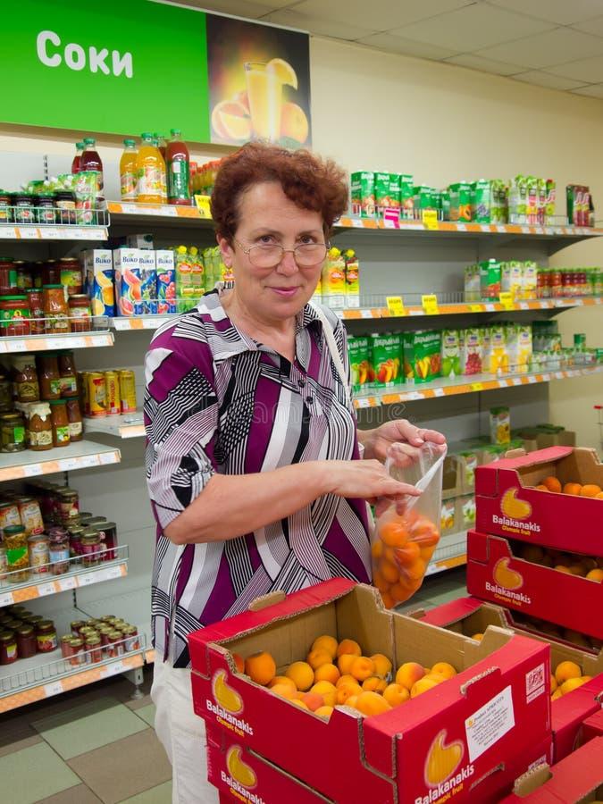 Voronezh, Ρωσία - 20 Ιουνίου 2013, η ώριμη γυναίκα επιλέγει τα φρούτα στην υπεραγορά στοκ εικόνες
