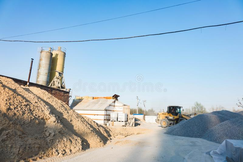 Voronezh region, Russia, april, 25 2019. Tractor loads crushed stone in the production of concrete. Yellow tractor loader running stock images