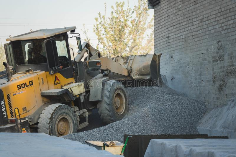 Voronezh region, Russia, april, 25 2019. Tractor loads crushed stone in the production of concrete. Yellow tractor loader running royalty free stock photography