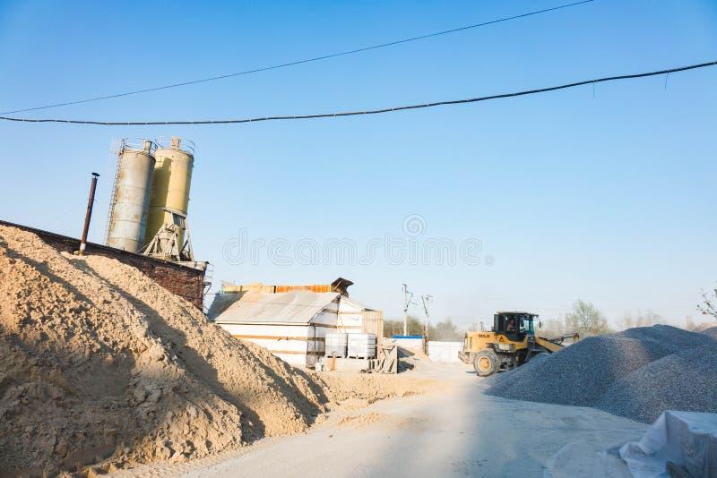 Voronezh-Region, Russland, April, 25 2019 Traktorlasten zerquetschten Stein in der Produktion des Betons Gelber Traktorladerbetri stockbilder