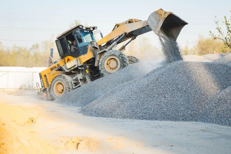 Voronezh region, Ryssland, april, 25 2019 Traktorp?fyllningar krossade stenen i produktionen av betong Gul traktorladdarspring royaltyfri foto