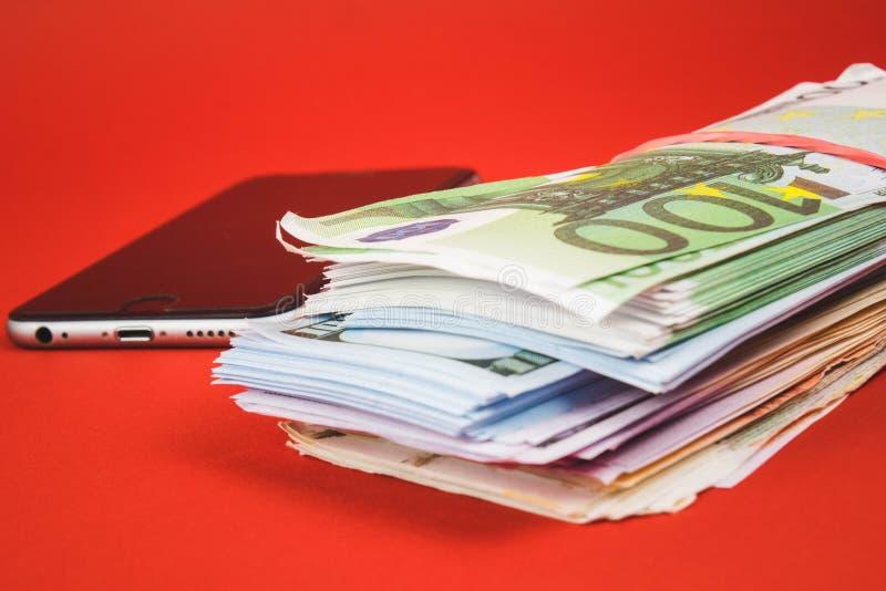 Voronezh Rosja, Kwiecie?, - 30, 2019: Jab?czany iPhone telefon kom?rkowy k?a?? na dolar?w rachunkach jab?czany ilustracyjny imac  zdjęcie royalty free