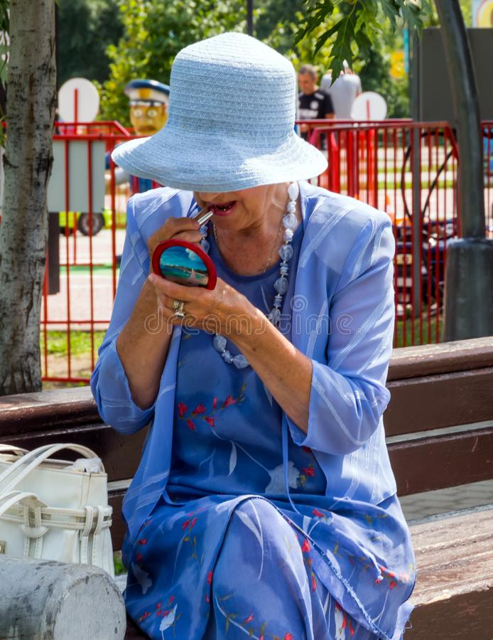 An elderly woman paints her lips while sitting on a bench stock images