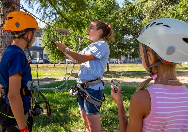 Instructing children on safety measures in the rope park stock photos