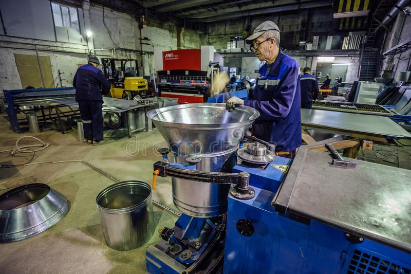 Voronezh, Russia - December 18, 2018: Worker in metalworking plant finishing of forming pipe part stock photo