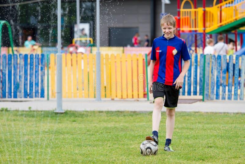 Voronezh Ryssland: Juni 17, 2013 En pojke spelar fotboll på en varm solig dag fotografering för bildbyråer