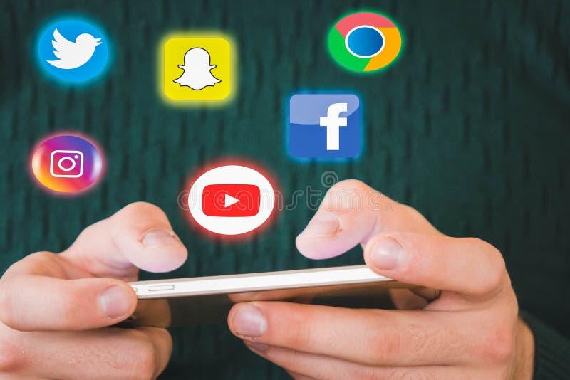 Voronezh Ryssland - kan 5, 2019 rymmer en person telefonen i hans hand och symbolerna av Facebook, Snapchat, Instagram, Twitter, royaltyfri illustrationer
