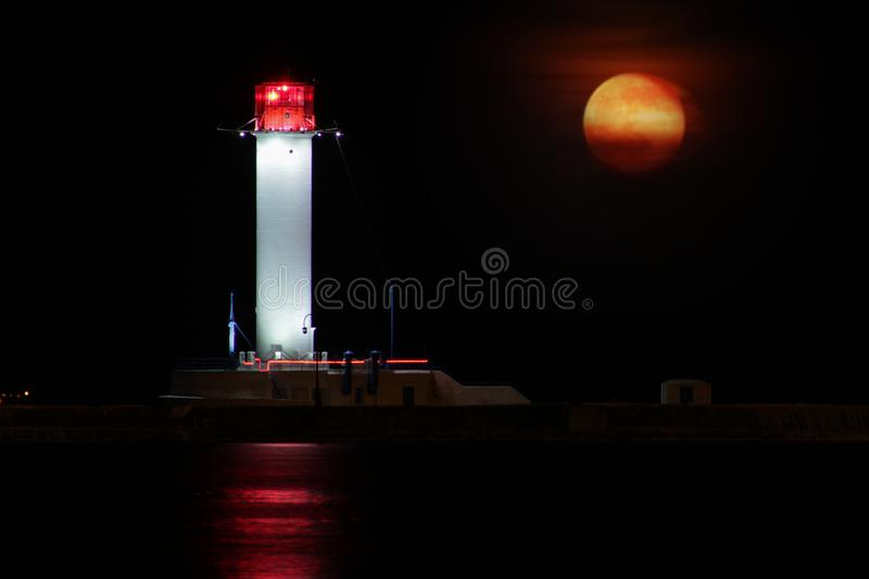 Vorontsov Lighthouse night against the rising of the big red moon. royalty free stock photo