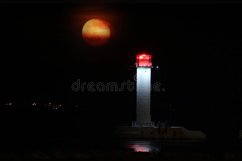 Vorontsov Lighthouse night against the rising of the big red moon. stock photo