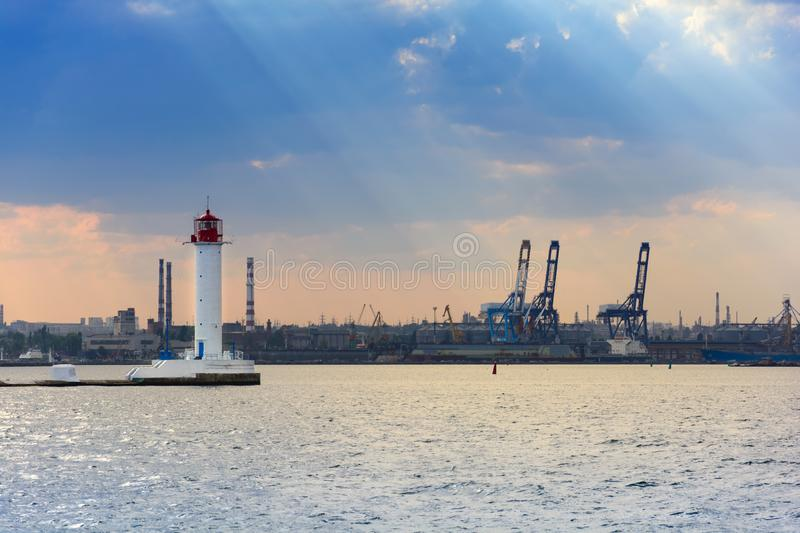 Vorontsov Lighthouse in the sea against the backdrop of a cargo port. Odessa, Ukraine royalty free stock photo