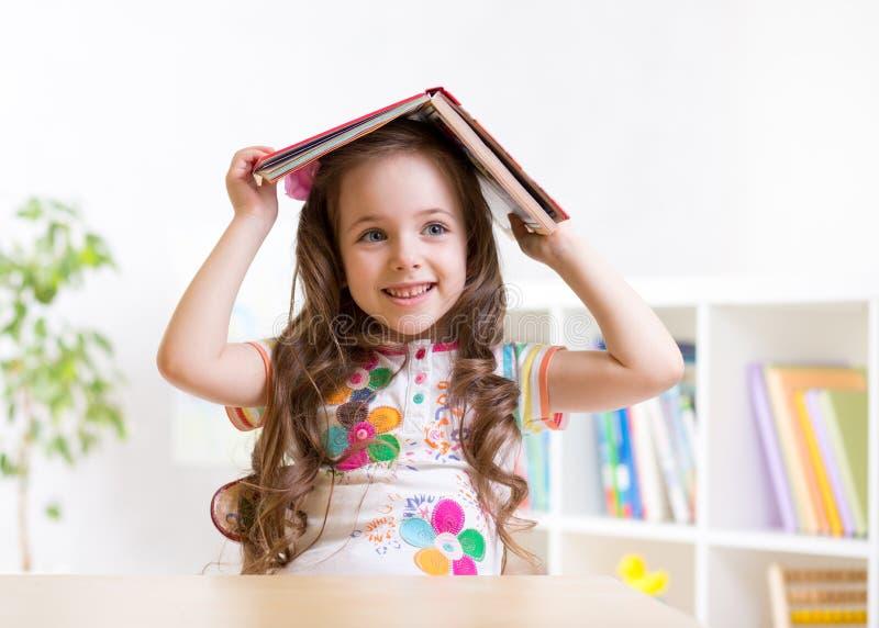 Vorschülerkindermädchen mit Buch über ihrem Kopf lizenzfreies stockfoto