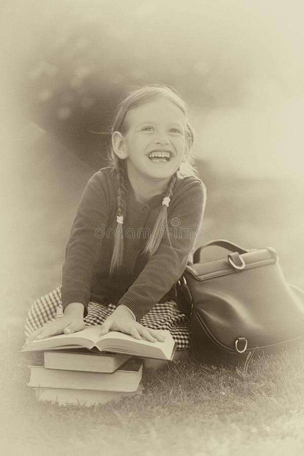 Vorschülermädchen bereit zurück zu der Schule, Lehrbücher lesend stockbilder