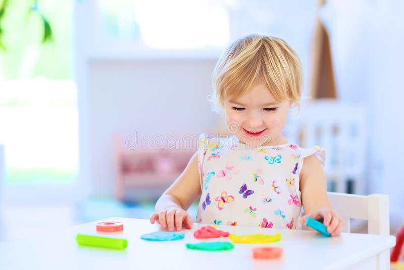 Vorschülermädchen, das mit Plasticine spielt lizenzfreie stockfotografie