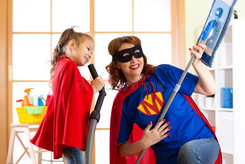 Vorschülermädchen und ihre Mutter kleideten wie Superhelden an Spielendes Frau von mittlerem Alter und Kind beim Reinigung zu Hau lizenzfreie stockfotografie