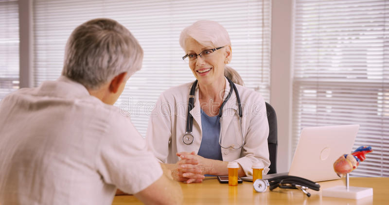 Vorschreibende Medikation der freundlichen Ärztin zum älteren Patienten lizenzfreie stockfotografie
