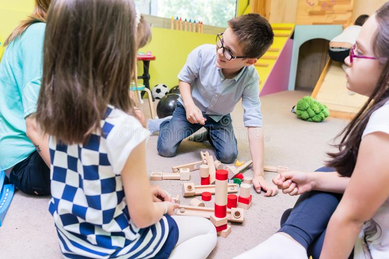 Vorschule- Junge, der mit Kindern unter Anleitung der Kindergärtnerin zusammenarbeitet stockbild