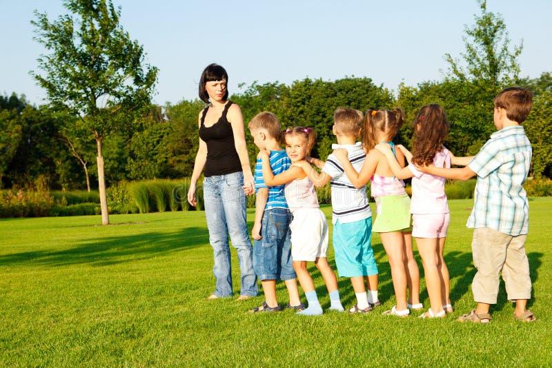 Vorschuljungen und Mädchen mit Lehrer stockfotografie