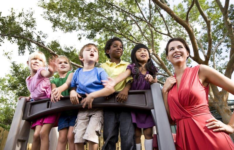 Vorschulkinder auf Spielplatz mit Lehrer stockfotografie